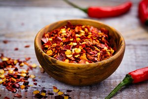 Red hot pepper flakes in a wooden mortar and pepper pods on wooden table