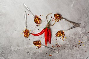 Bunch of red hot chilli peppers and flakes in spoons on grey stone kitchen table