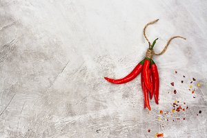 Abstract background with red hot chilli pepper pods and flakes on blue