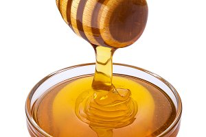 Honey dipper and bowl of pouring honey isolated on white background