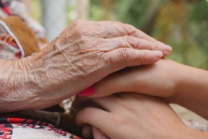 Old wrinkled and young female hands comforting and stroking each other outdoor. Granddaughter and grandmother spending time together outside. Caring and loving concept. Close up Side view Slow motion