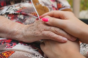 Young female arms with beautiful manicure comforting an elderly pair of old woman hands. Granddaughter and grandmother spending time together outside. Caring and loving concept. Close up Slow motion