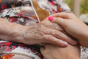 Young girl with beautiful manicure holding wrinkled hands of old woman outdoor. Granddaughter and grandmother spending time together outside. Caring and loving concept. Close up Slow motion