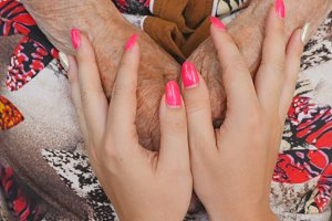 Young female arms with beautiful manicure comforting an elderly pair of old woman hands. Granddaughter and grandmother spending time together. Caring and loving concept. Close up Top view Slow motion