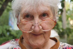 Old woman in eyeglasses looking into camera and smiling outdoor. Portrait of happy granny in glasses spending time outside. Emotions of grandmother. Close up Slow motion