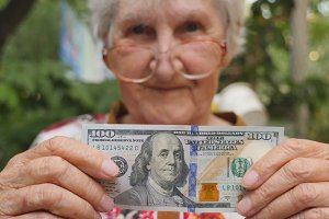 Old woman in eyeglasses showing one hundred dollar bill into camera outdoor. Happy grandmother holding foreign currency outside. Money concept. Close up Slow motion