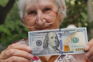 Old woman in eyeglasses showing one hundred dollar bill into camera and smiling outdoor. Granny holding cash outside. Money concept. Close up Slow motion