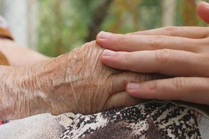 Young male arms comforting an elderly pair of old woman hands outdoor. Grandson and grandmother spending time together outside. Caring and loving concept. Close up Side view Slow motion