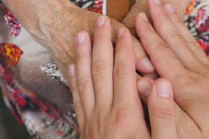 Young male arms comforting an elderly pair of old woman hands. Grandson and grandmother spending time together. Caring and loving concept. Close up Top view Slow motion