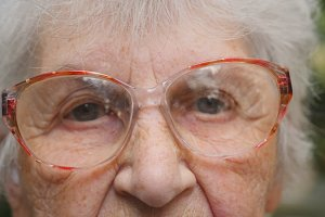 Dolly shot of old woman in glasses outdoor. Eyes of an elderly lady with wrinkles around them. Close up portrait of grandmother outside. Slow motion