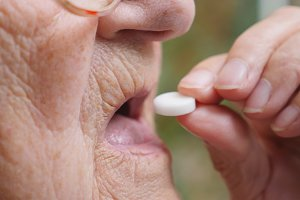 Old woman in glasses putting white pill in her mouth. Close up Side view Slow motion