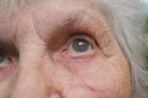 Close up portrait of old woman looking up. Eyes of an elderly lady with wrinkles around them. Slow motion