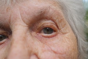 Close up portrait of old woman watching into camera and then looking up. Eyes of an elderly lady with wrinkles around them. Slow motion