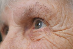 Old woman looking into the distance. Eyes of an elderly lady with wrinkles around them. Close up portrait of grandmother. Slow motion