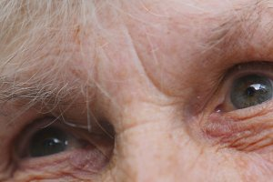 Eyes of an elderly lady with wrinkles around them. Old woman looking into the distance. Close up portrait of sad grandmother. Slow motion