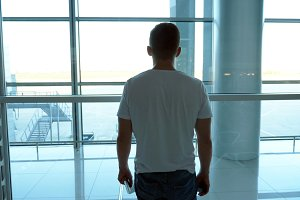 Young man standing in terminal of airport and looking at window. Guy waiting for his airplane. Rear back view Slow motion