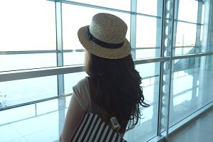Young woman in hat with backpack standing in terminal of airport and looking at window. Girl waiting for her airplane. Tourism and travel concept. Rear back view Slow motion