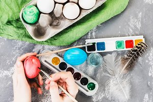 Young mother painting Easter eggs