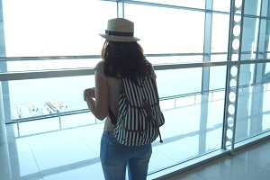 Young woman in hat with backpack standing in terminal of airport and looking at window. Girl waiting for her airplane and then leaves. Tourism and travel concept. Rear back view Slow motion