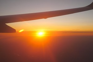 View from airplane window to beautiful sunrise or sunset. Wing of plane and cloud in sky. Travel concept. Close up