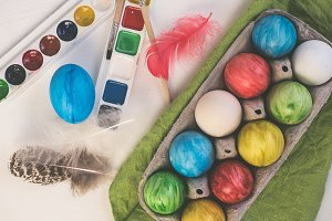 Painted easter eggs on a white, wooden table