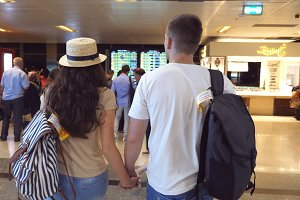 Young couple walking to aircrafts timetable at airport. Pair checking airline departure at terminal. Rear back view Slow motion