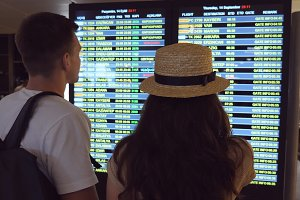 Young couple looking at flight schedule at airport. Pair checking airline departure at terminal. Man pointing something to his girlfriend at timetable board screen. Slow motion Rear back view