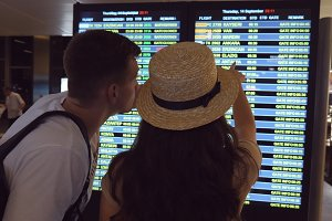 Woman pointing something to his boyfriend at timetable board screen. Young couple looking at flight schedule at airport. Pair checking airline departure at terminal. Slow motion Rear back view