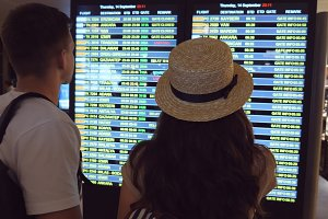 Young couple looking at flight schedule at airport. Pair checking airline departure at terminal and then leaves. Slow motion Rear back view