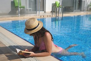 Beautiful girl in hat and sunglasses reading book at pool. Young woman relaxing at warm sunny day during vacation. Summer holiday concept. Side view Close up Slow motion