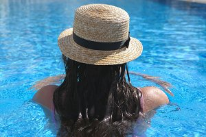Back of young unrecognizable girl in hat swimming in pool. Woman relaxing in basin. Holiday concept. Rear view Close up Slow motion