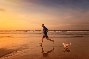 Owner and dog running at the beach