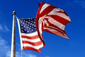 waving american flag over blue sky