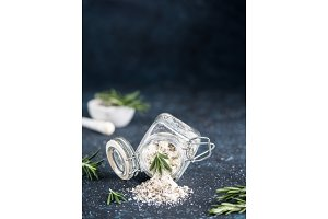 Sea salt scented herb rosemary on dark blue background