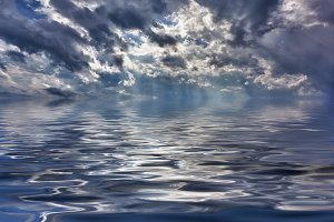 Backgrond image of stormy sky over a calm and reflective ocean