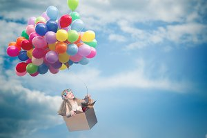 Happy girl flying in a cardboard box on the balloons