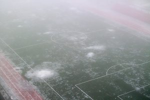 Football field in the fog and melting snow