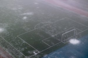 Football goal in the fog in the school stadium. Melting snow