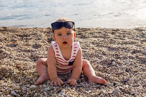 baby boy in hat on beach pebbles