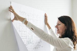 A woman sticking a blueprint