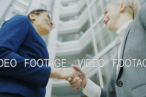 Low angle shot of businesswoman shaking hands and talking with female business colleague in suit in hall of modern office building