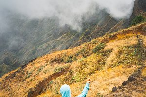 Traveler staying on the cobbled path and admiring clouds flowing over the mountain peaks into the valley. Santo Antao island in Cabo Verde