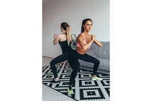 Two fit women doing squats at home Female workout sport and fitness