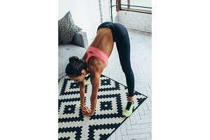 Fitness woman back stretching training at home. Young slim girl makes forward bend