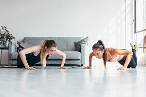 Two fitness women warming up doing push-ups exercise working out at home