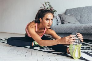 Fit woman doing stretching while sitting on the floor at home