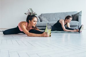 Sportswomen warming-up muscles before workout doing stretching exercise sitting on floor at home