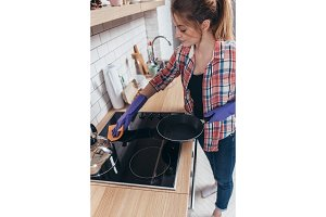Young woman cleaning countertop in the kitchen