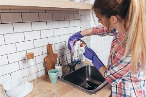 Woman washing the kitchen sink and faucet