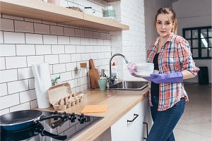 Portrait of a young beautiful housewife holding a pile of clean dishes and looking at camera